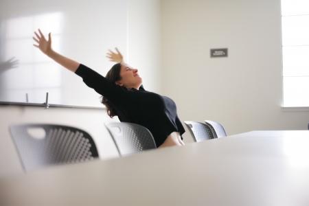 office break: Mujer joven feliz que estira en sala blanca presentaci�n de la oficina.