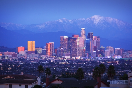 los angeles: Downtown Los Angeles skyline over snowy mountains at twilight.