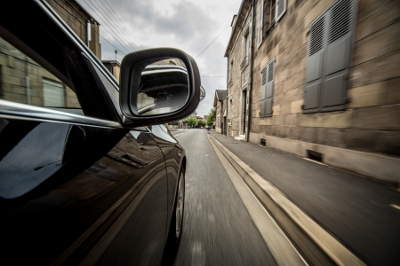 europe: Car driving in old European town in French.
