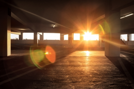 Sun peeking into large dark empty grunge parking structure inter. Stock Photo - 18753157