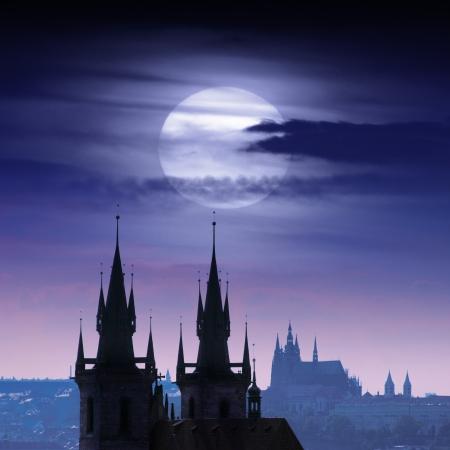 Full moon over Prague castles skyline at night.