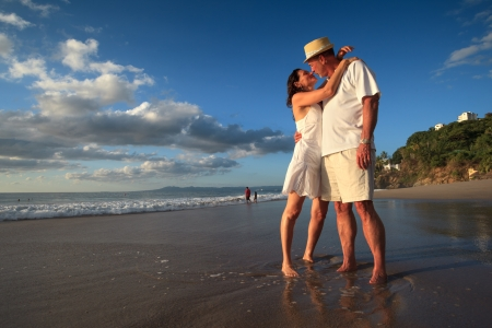 Mature senior adult couple kiss on tropical beach standing in ocean water. photo