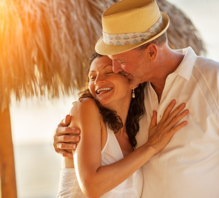 Happy Caucasian mature senior adult couple kiss on tropical beach, closeup.