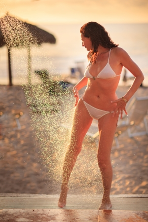 Beautiful mature adult woman enjoying shower on tropical beach resort at sunset