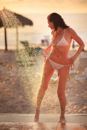 Mooie rijpe volwassen vrouw te genieten van douche op tropische beach resort bij zonsondergang