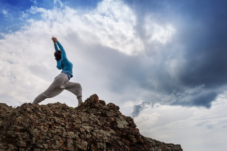 Young woman in yoga pose standing on mountain rock under beautiful cloudy sky. Standard-Bild