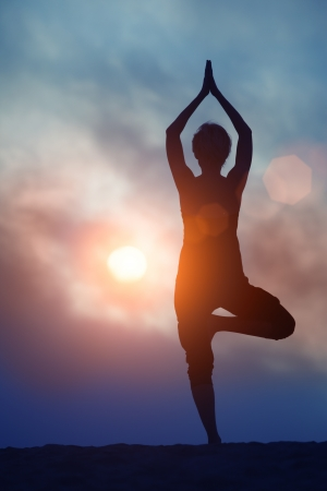 Woman doing yoga Tree pose over sunrise sky background photo