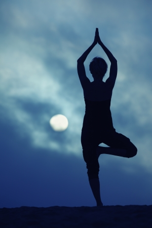 full figure: Woman in yoga Tree pose over blue night sky background Stock Photo