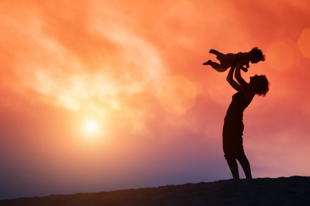 Mother lifting toddler child in air over scenic sunset sky
