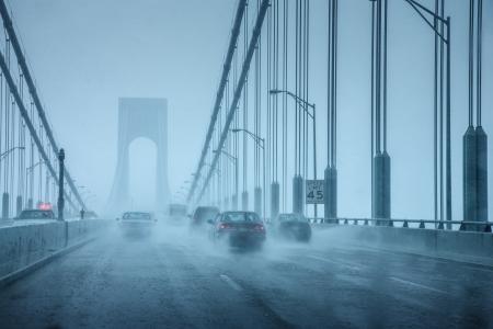 Auto's rijden in zware regen op hangbrug