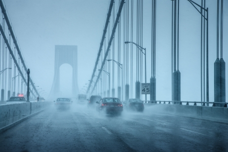 Cars driving in heavy rain on suspension bridge