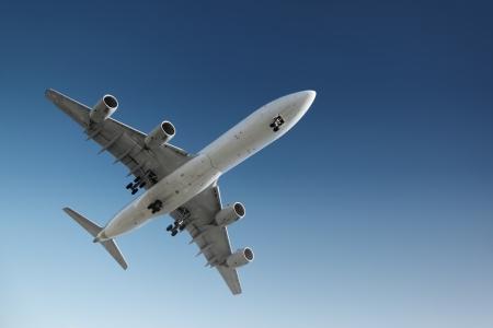 Jet plane flying in blue sky, preparing for landing.
