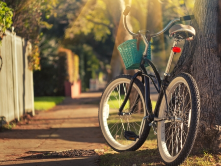 Retro gestileerde fiets op zonnige straat. Ondiepe DOF, focus op achterwiel.