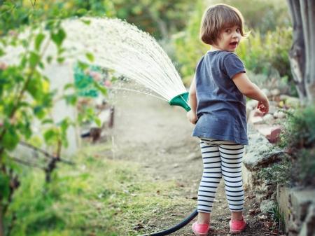 watering garden: Little happy girl watering garden