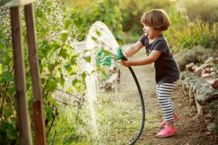 Little happy girl watering garden