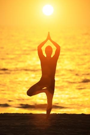 yoga man: Man standing in yoga tree pose on ocean beach at sunset Stock Photo