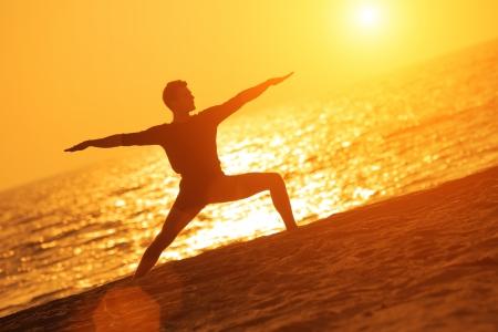 Man in yoga warrior pose on ocean beach at sunset