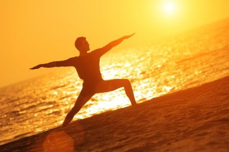 man outdoors: Man in yoga warrior pose on ocean beach at sunset