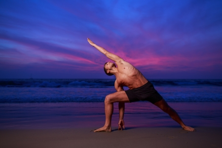 Man in stretching yoga pose on ocean beach at dusk photo