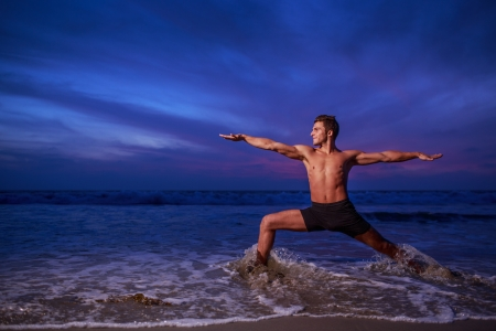 Man in yoga warrior pose on ocean beach at dusk photo