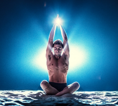 humanities: Man meditating in yoga pose, surrounded by rays of light  Stock Photo