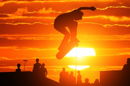 Skater on skateboard jumping over sunset sky photo