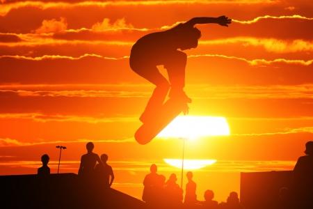 Skater on skateboard jumping over sunset sky Stock Photo - 24286114