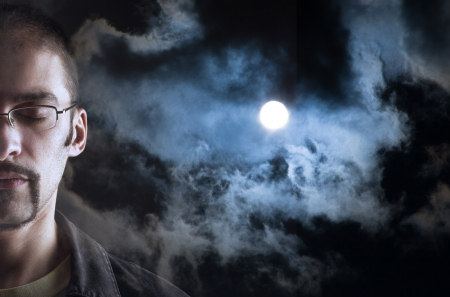 ojos cerrados: Hombre soñando con los ojos cerrados de la luna en el cielo nublado detrás de su cara Foto de archivo