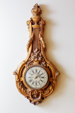 Vintage royal ornate luxury clock on white wall background. photo