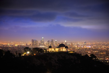 Los Angels city skyline at night with Griffith Observatory in foreground and downtown in background.