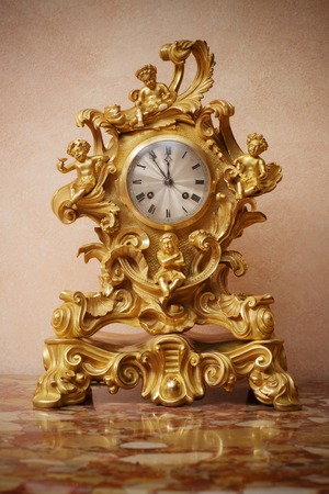 Vintage ornate golden clock on marble table, closeup.