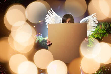 Angel woman with white wings holding blank cardboard message board poster over glowing golden lights background. 版權商用圖片