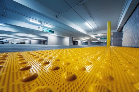 Grunge industrial room interior with safety yellow bumps panel on floor. Copyspace.