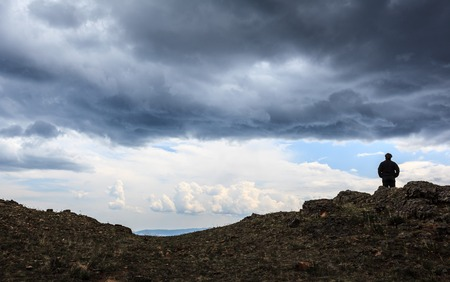 Man on top of mountain under stormy cloudy sky background