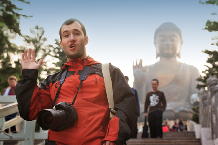 Happy caucasian tourist near Big Buddha statue landmark at Lantau Island,Hong Kong, China. Asia.