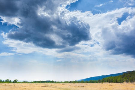 Beautiful clouds in blue sky over field steppe landscape in Siberia. 版權商用圖片