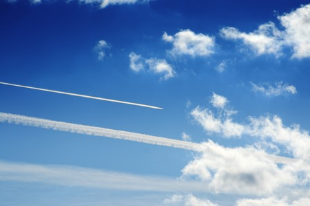 Jet trails  and white clouds over blue sky background