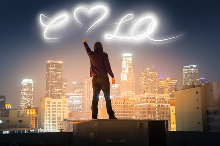Graffiti artist on rooftop in downtown Los Angeles painting love LA message over night sky with light. photo
