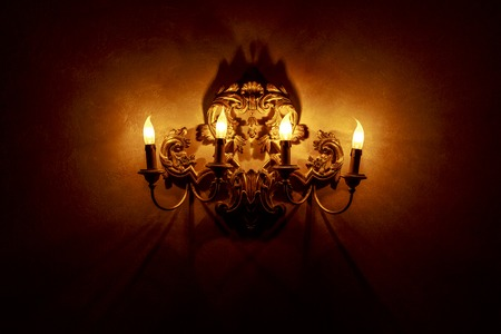 Vintage style lamp with candlesticks illuminating dark wall background photo