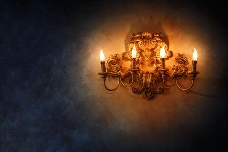Vintage style lamp with candlesticks illuminating dark wall background