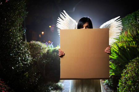 Angel woman with white wings holding blank cardboard message board poster in night garden. Copyspace.