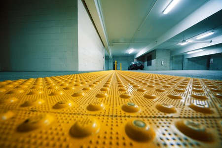braille: Grunge industrial room interior with safety yellow bumps panel on floor. Copyspace.