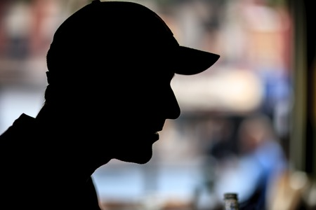 Silhouette of man in baseball cap indoors over bokeh blur background. Closeup, copyspace. 版權商用圖片