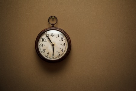 Retro clock on brown wall background