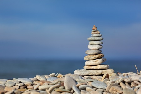 Stack of zen stones on pebble beach against blue water and sky background 版權商用圖片