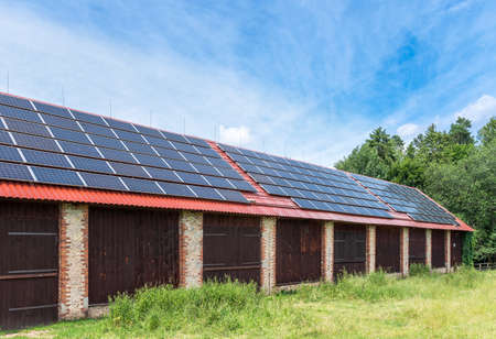 Brick barn in a countryside. Solar panels installed on the roof of the barn.