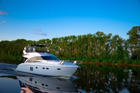 recreation yachts: Pleasure boat floats in the evening on the river Volga Stock Photo