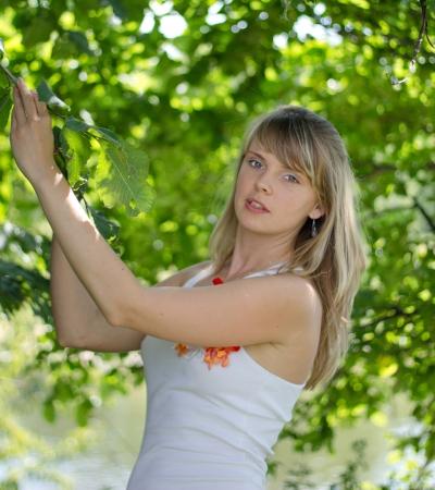 Beautiful girl standing among the trees on a sunny day Stock Photo
