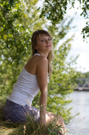 The beautiful girl sitting on the bank of the river on a sunny day