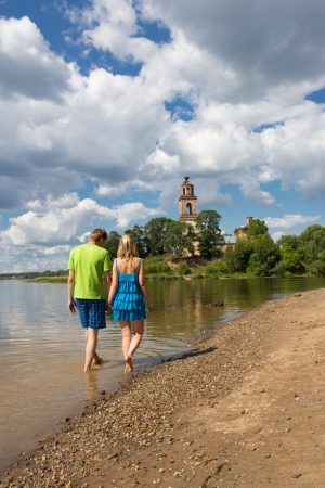 Beautiful girl walking with a young, confident guy on the river in the countryside
